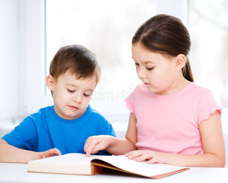 Barn är läseboken royaltyfri fotografi