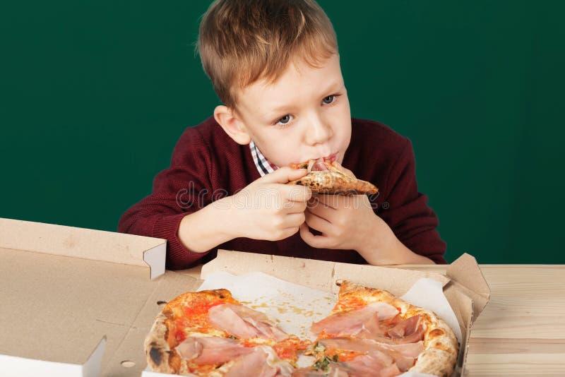Barn äter italiensk pizza i kafét Skolapojken äter piz royaltyfria foton