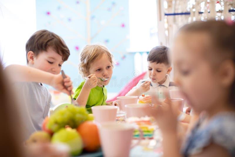 Barn äter kakan på födelsedagpartiet arkivbilder