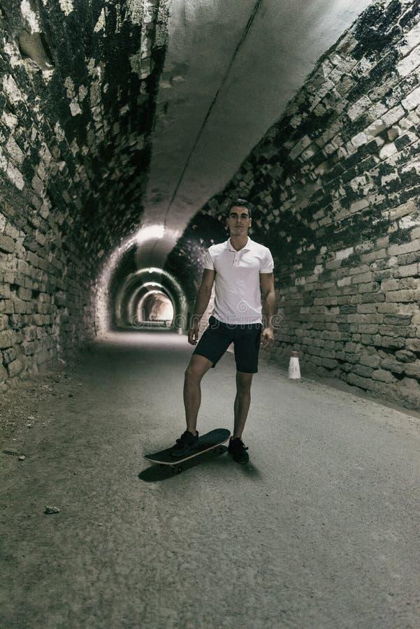 Barn 20-25 år gamal man i tunnel med skateboarden Omgivande lig royaltyfria foton