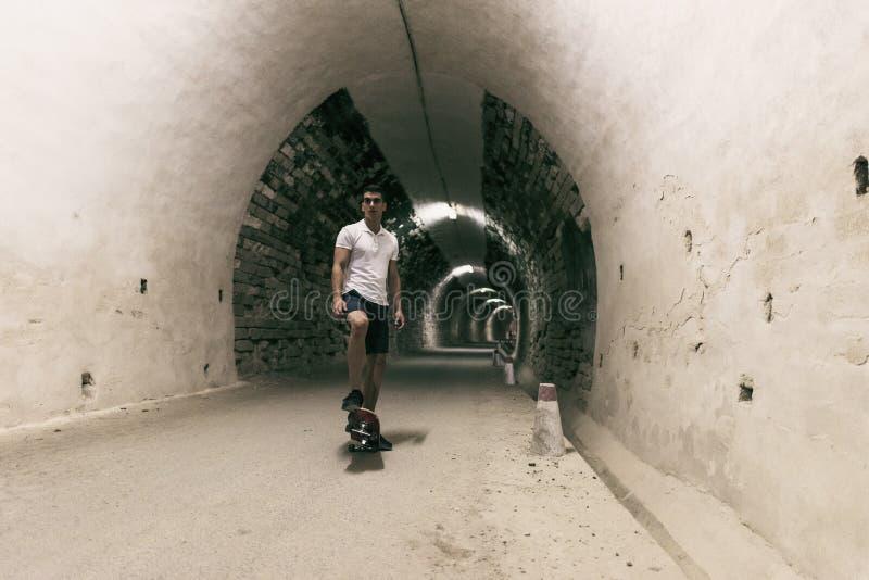 Barn 20-25 år gamal man i tunnel med skateboarden Omgivande lig royaltyfria bilder