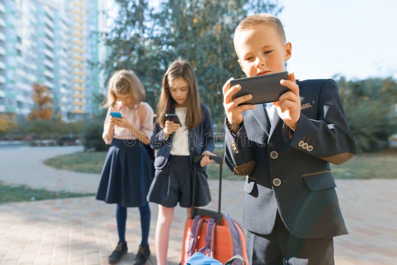 Barn av den elementära åldern med smartphones, ryggsäckar, utomhus- bakgrund Utbildning, kamratskap, teknologi och folkbegrepp fotografering för bildbyråer