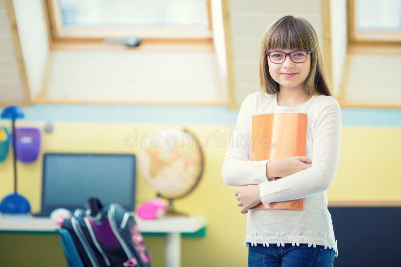 Barn av den härliga pre-tonåriga flickan med häftet Ett barn som gör läxa royaltyfria bilder