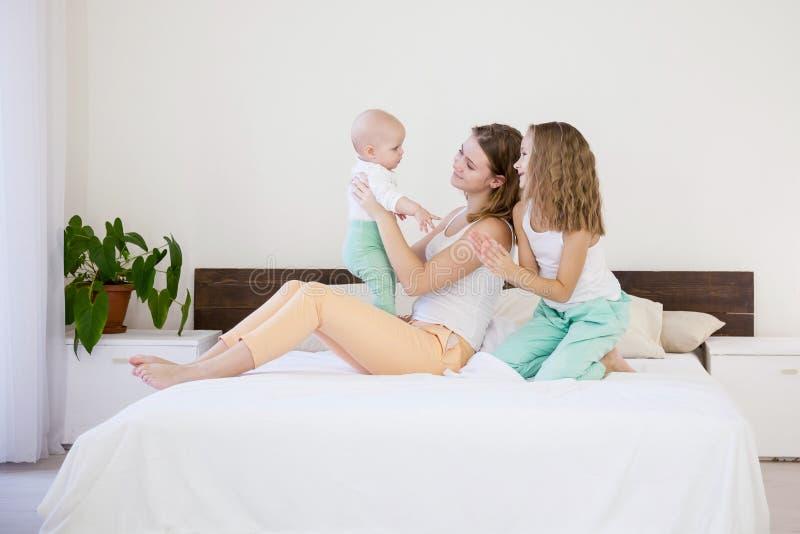 Barn av tre systrar i morgonen på sängen i sovrummet arkivbild