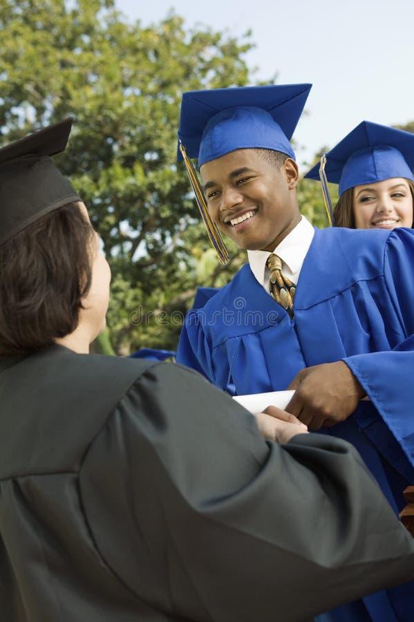 Barn avlägger examen samla certifikat från dekan royaltyfria bilder