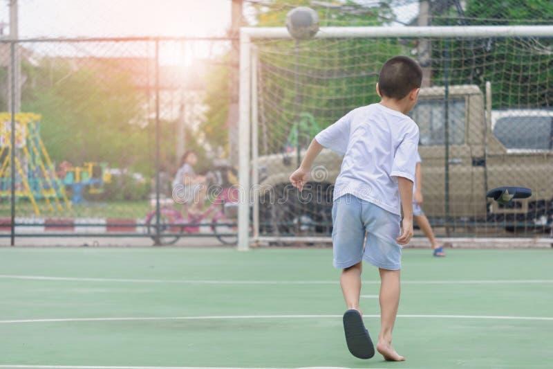 Barn bär häftklammermatare som spelar fotboll med suddig bakgrund för att visa rörelse Att att öva efter skola arkivbild