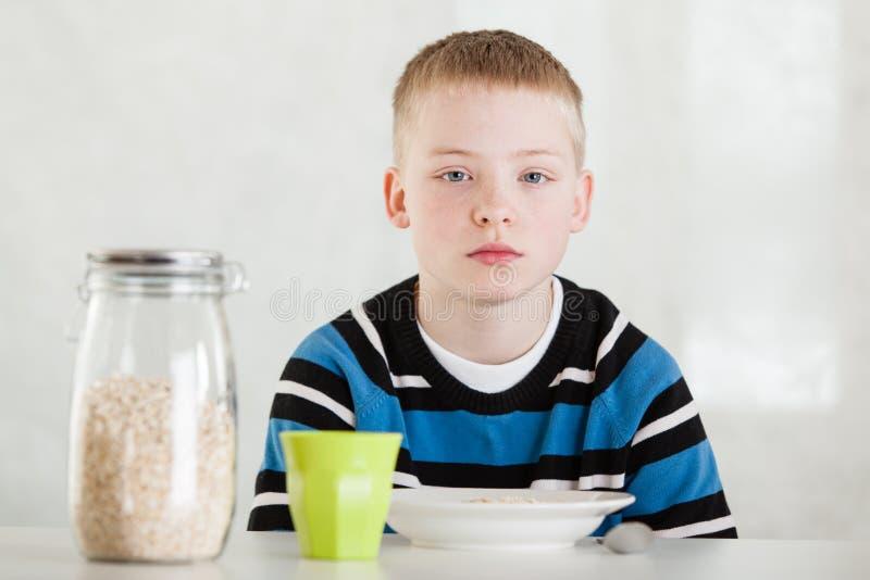 Barn bredvid kruset av havre, koppen och bunken på tabellen arkivfoto