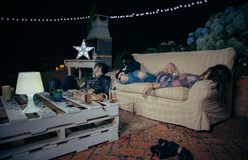 Barn drack vänner som sover i en soffa efter parti royaltyfria bilder