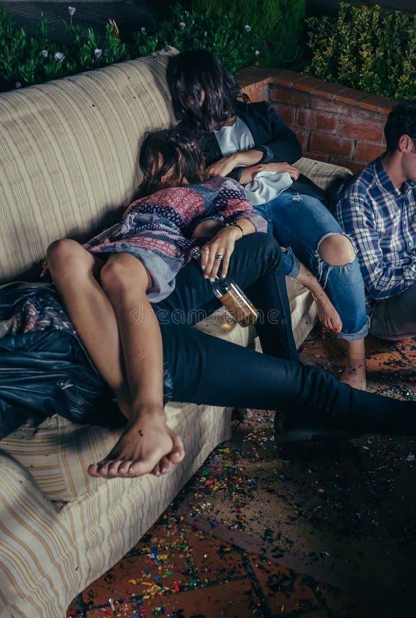 Barn drack vänner som sover i en soffa efter parti royaltyfria foton