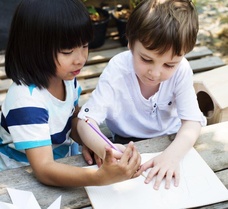 Barn drar någon idé tillsammans arkivbild