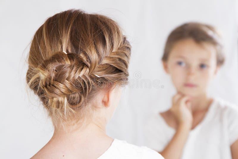 Barn eller ung flicka som stirrar på henne i en spegel royaltyfria foton