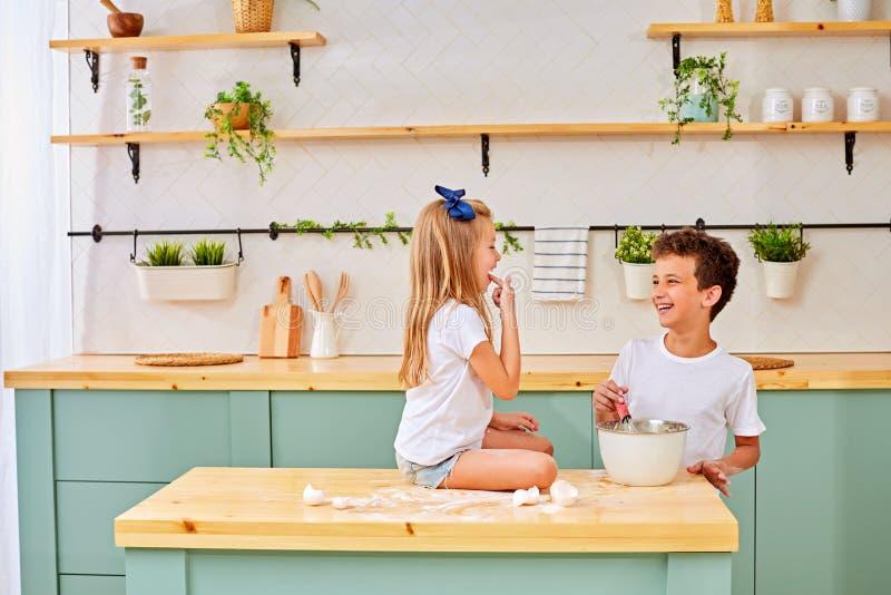 Barn en pojke och en flicka knådar en deg av mjöl och ägg och förbereder läckert royaltyfri fotografi
