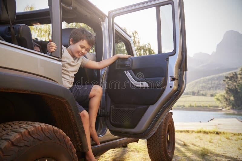 Barn får ut ur bilen, når de har nått sjön på drev för vägtur royaltyfri fotografi