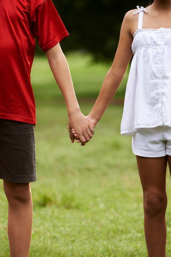 Barn förälskade pojke- och flickainnehavhänder royaltyfri foto