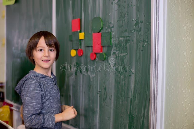 Barn för första kvalitet som lär matematik, former och färger på skola royaltyfri fotografi