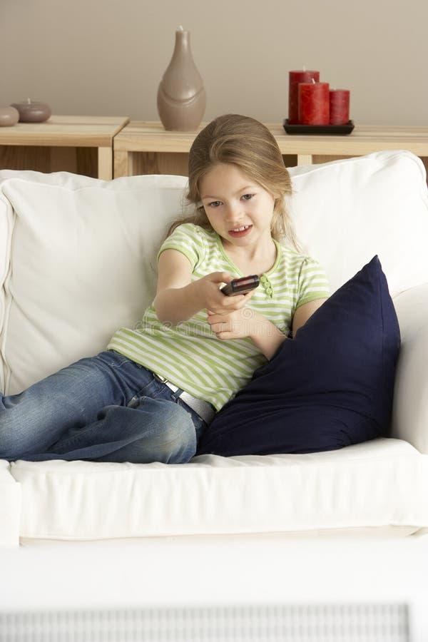 barn för home television för flicka hållande ögonen på arkivfoton