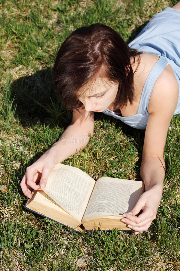 barn för kvinna för avläsning för bokgräs liggande avslappnande royaltyfria bilder