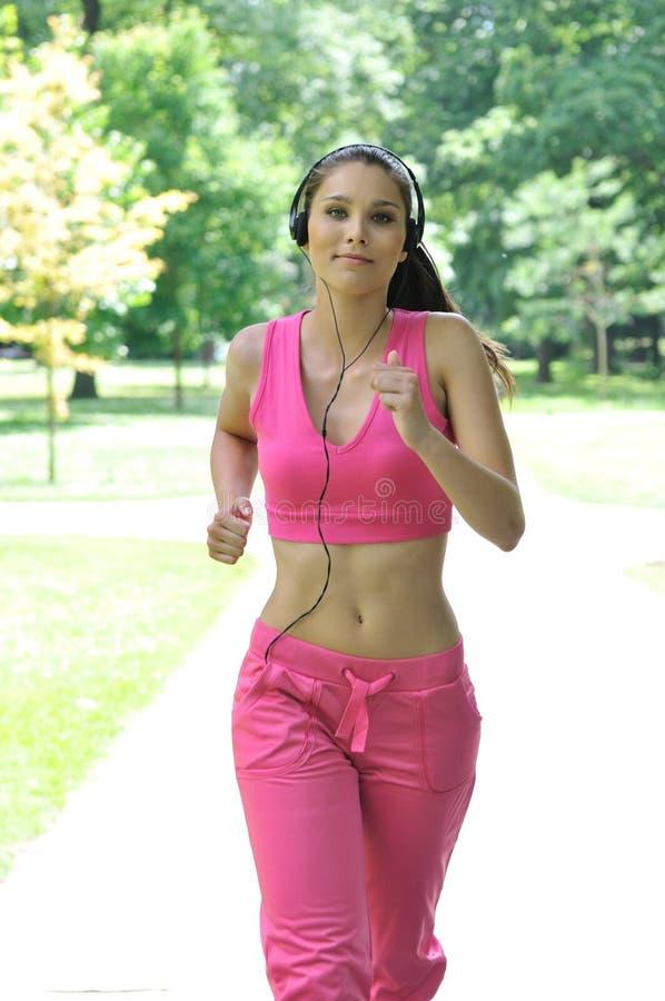 barn för kvinna för hörlurarpark running royaltyfria bilder
