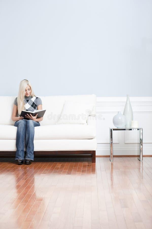 barn för kvinna för sofa för bokavläsning sittande arkivfoton