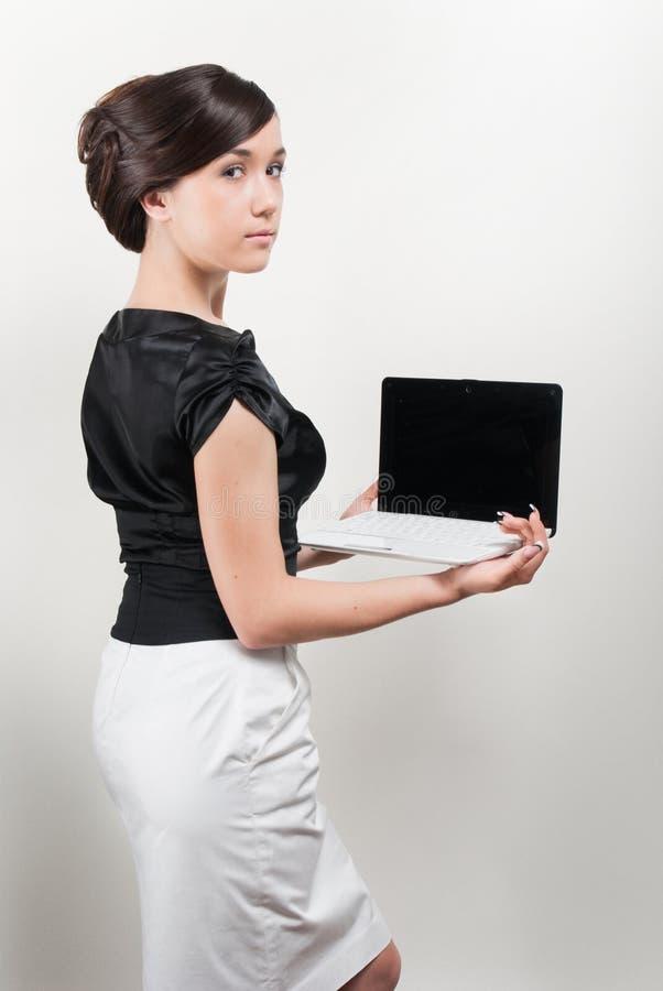 barn för kvinna för studio för holdingbärbar datorstående arkivfoto