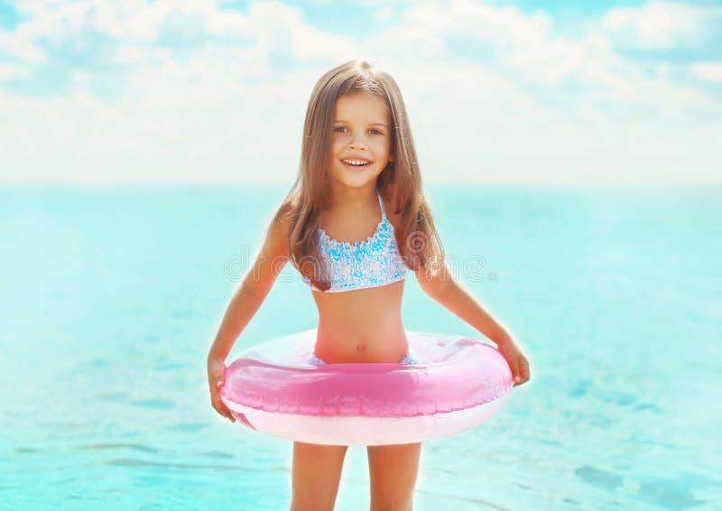 Barn för liten flicka för sommarstående som lyckligt badar med den uppblåsbara cirkeln som har roligt royaltyfri foto