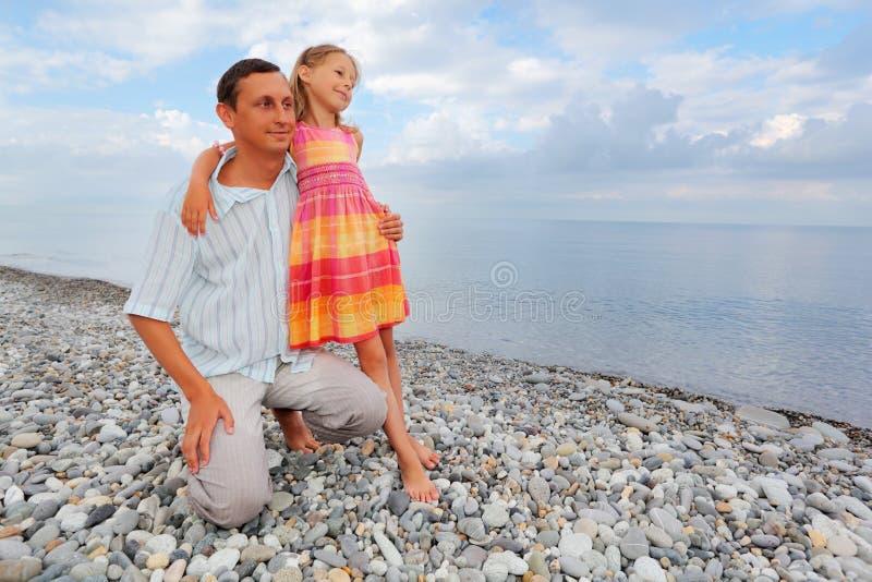 barn för liten man för strandflicka stenigt royaltyfri bild