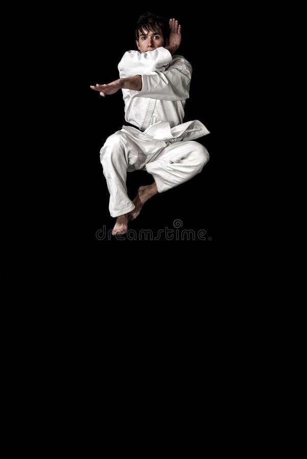 barn för manlig för karate för contrastkämpehöjdhopp arkivbild