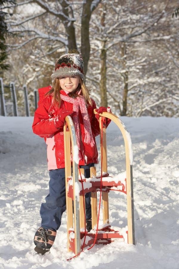 barn för pulka för flickaholdingliggande snöig royaltyfri bild