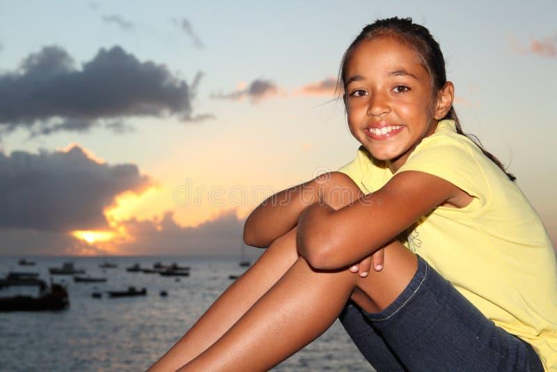 barn för solnedgång för lycklig sjösida för flicka sittande fotografering för bildbyråer