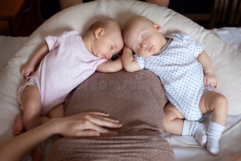 Barn för två spädbarn som vilar bredvid moder arkivbild