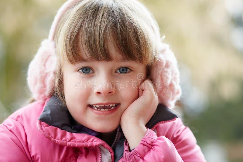 barn för utomhus- stående för öronskyddflicka slitage arkivbild