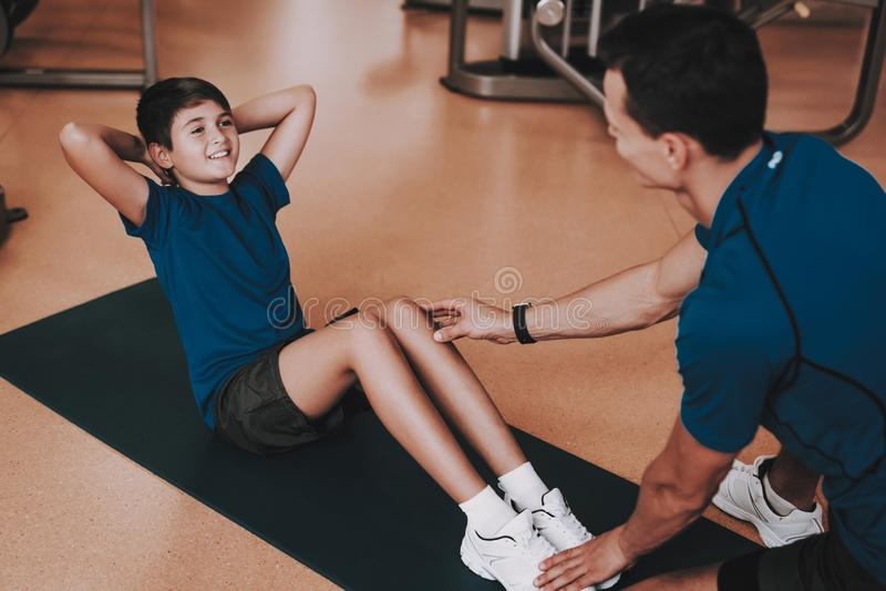 Barn fader och son som gör övningar i sportklubba arkivbilder