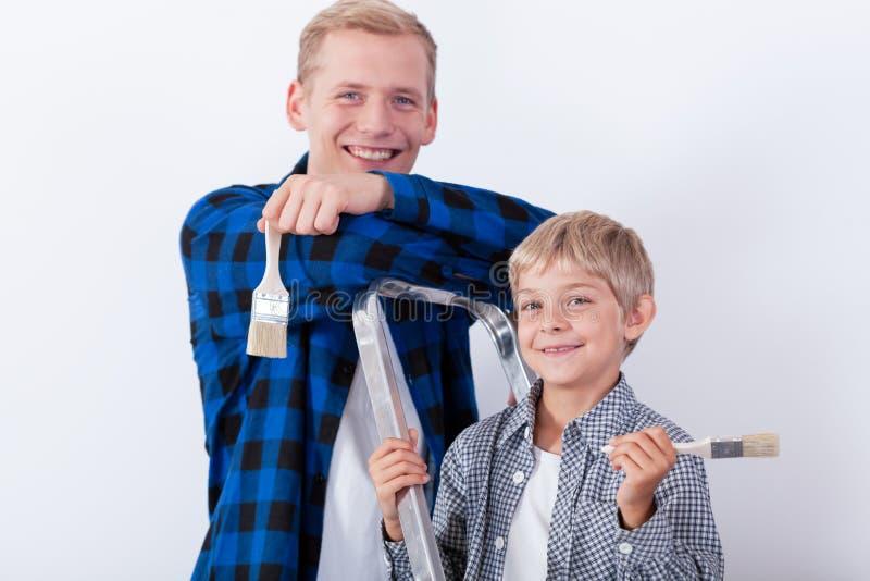 Barn fader och son under renovering royaltyfria foton