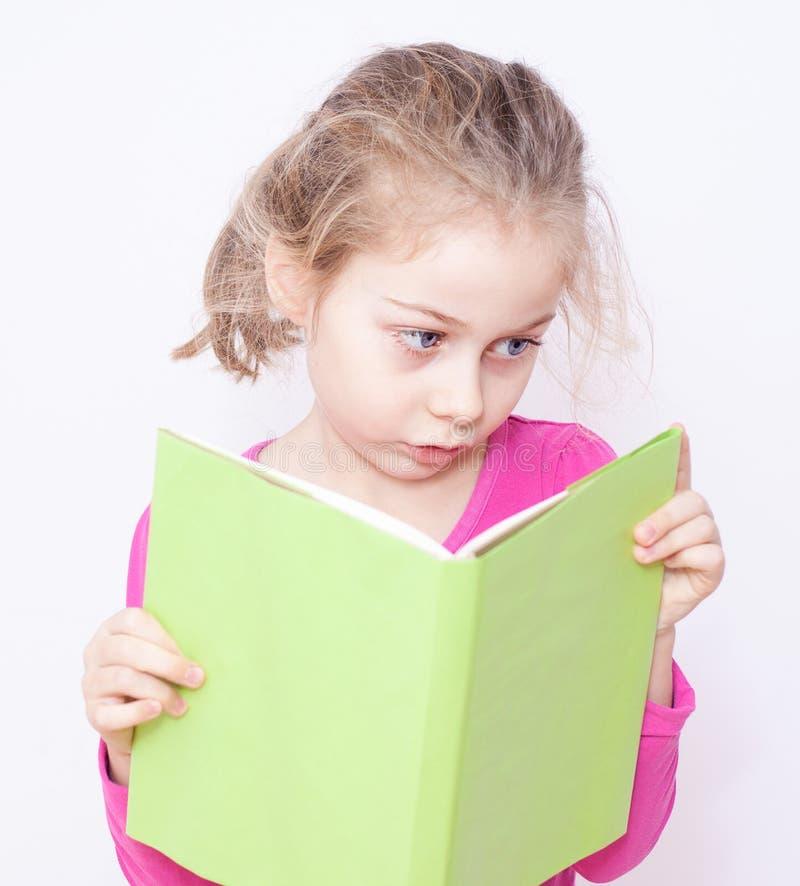 Barn fem år gammal barnflicka som läser en bok royaltyfri bild