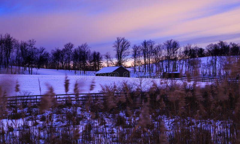 Barn and field in an evening snow storm with sun setting. Barn, fence, trees, and hill after an evening snow storm in Hudson Valley NY as the sun sets stock images