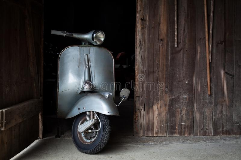 Barn find of old, rusty italian scooter in a hut. Barn find of old, rusty blue-grey colored italian scooter in a hut royalty free stock image