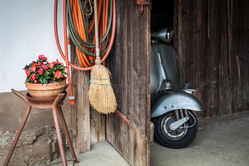 Barn find of old, rusty italian scooter in a hut. Barn find of old, rusty blue-grey colored italian scooter in a hut royalty free stock photo