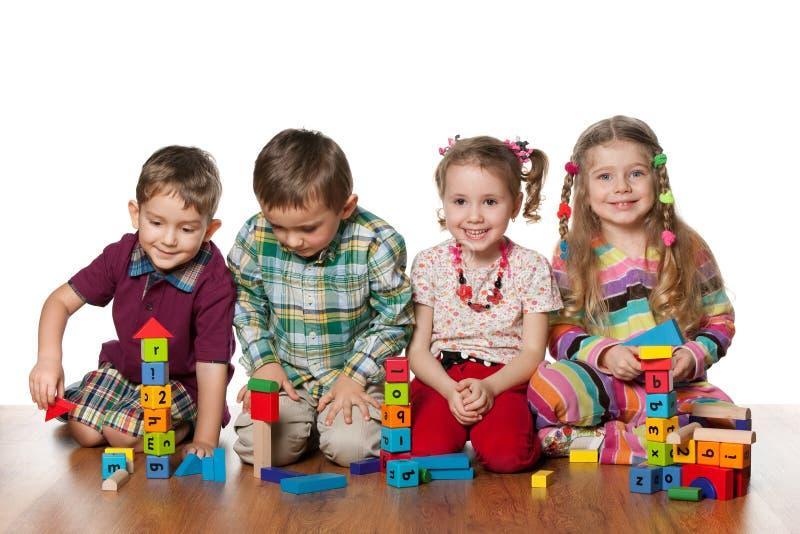 barn floor fyra som leker arkivfoton