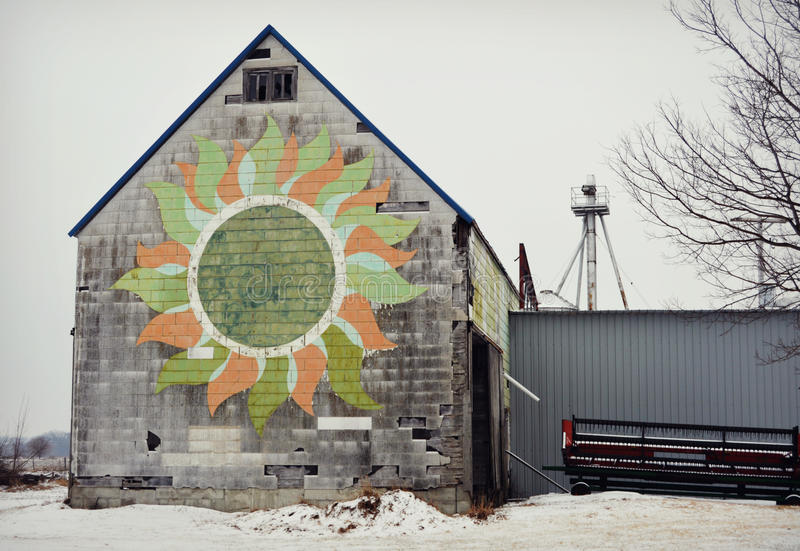 Barn With Flower. A rustic, old, white barn in the snow with a beautiful hand painted flower on the front with green white coral colors on it. Located in royalty free stock photo
