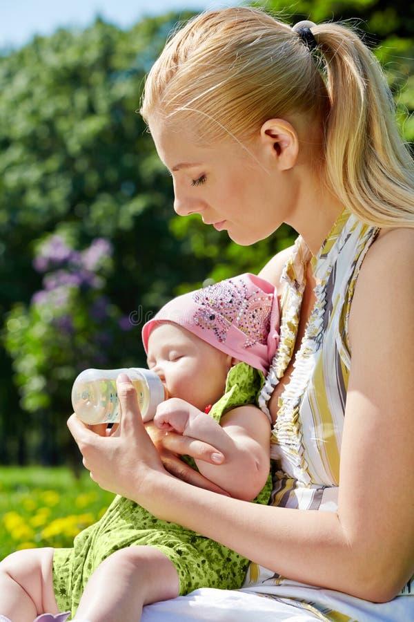Barn fostrar matningar behandla som ett barn från buteljerar fotografering för bildbyråer