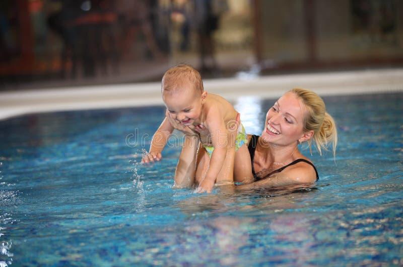 Barn fostrar och lite sonen som har gyckel i en simbassäng royaltyfri foto