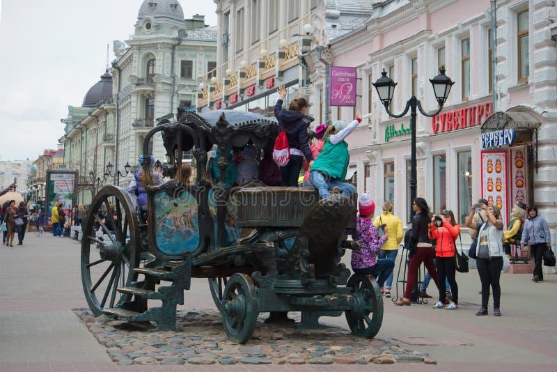 Barn fotograferas på en kopia av vagnen av kejsarinnan Catherine II på gatan Bauman kazan royaltyfri foto