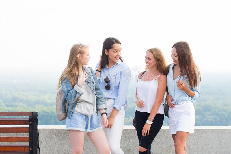 Barn fyra studentflickor som talar i parkera efter högskola Kvinnaleendet, jublar, har gyckel arkivbilder