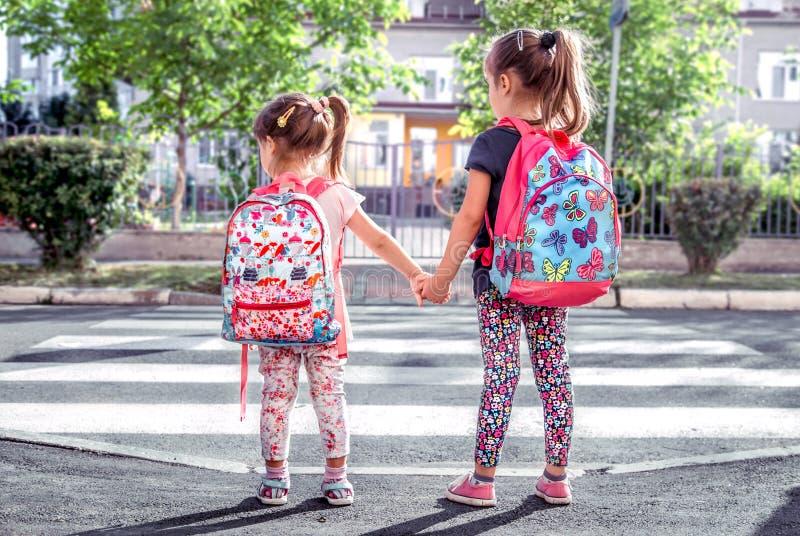 Barn går till skolan, lyckliga studenter med skolaryggsäckar och innehavhänder tillsammans arkivbild
