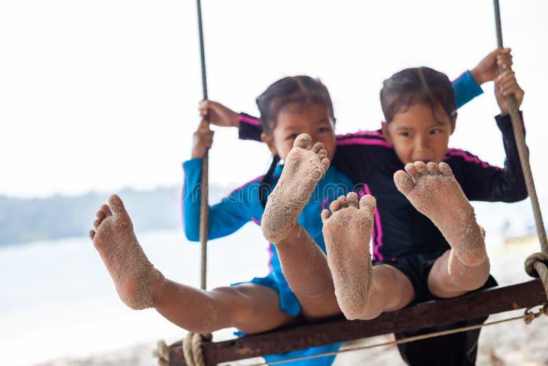 Barn g?r bar fot med sand medan dem som tillsammans spelar p? gungor p? stranden n?ra havet i semester arkivbilder