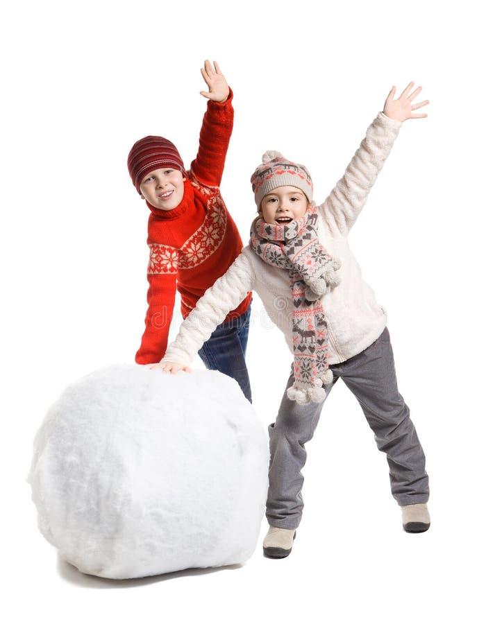 Barn gör en snögubbe i vintertid som isoleras arkivfoton