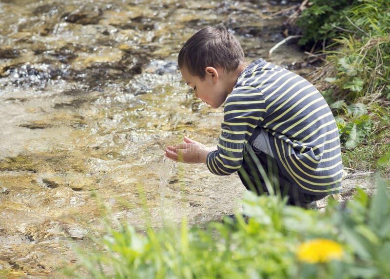 Barn, genom att spela i flodvatten arkivfoto