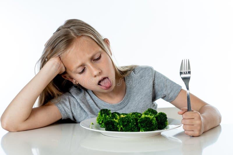 Barn gillar inte att äta grönsaker i sunt ätabegrepp arkivbild