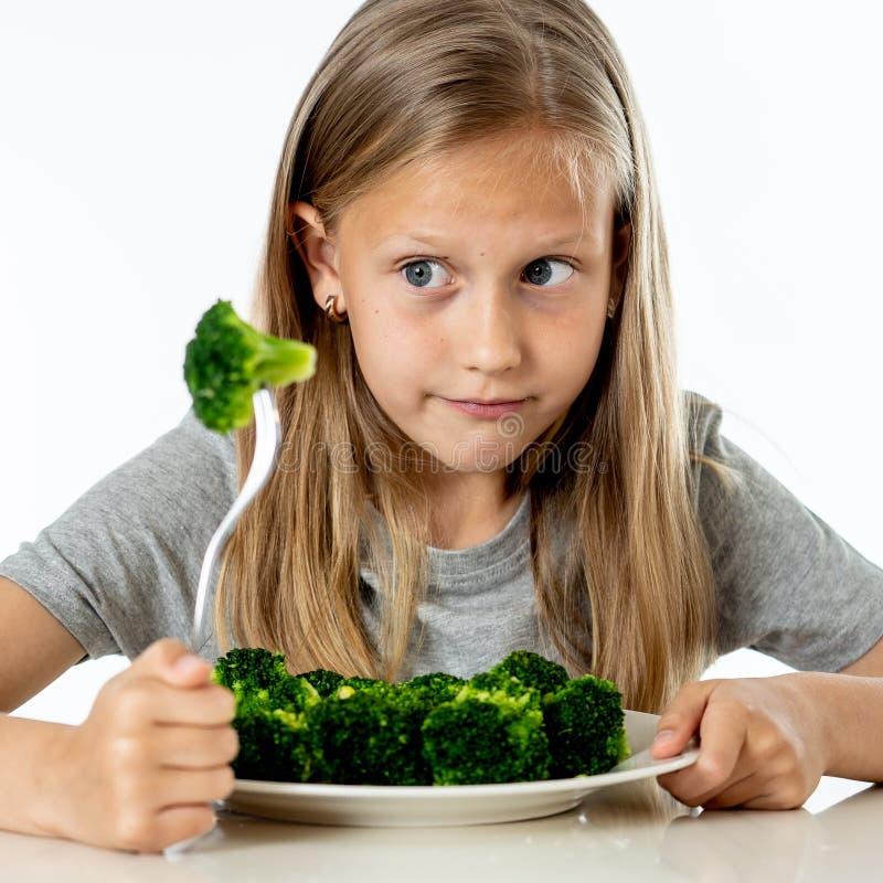Barn gillar inte att äta grönsaker i sunt ätabegrepp arkivfoton