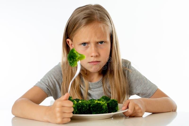 Barn gillar inte att äta grönsaker i sunt ätabegrepp royaltyfri foto